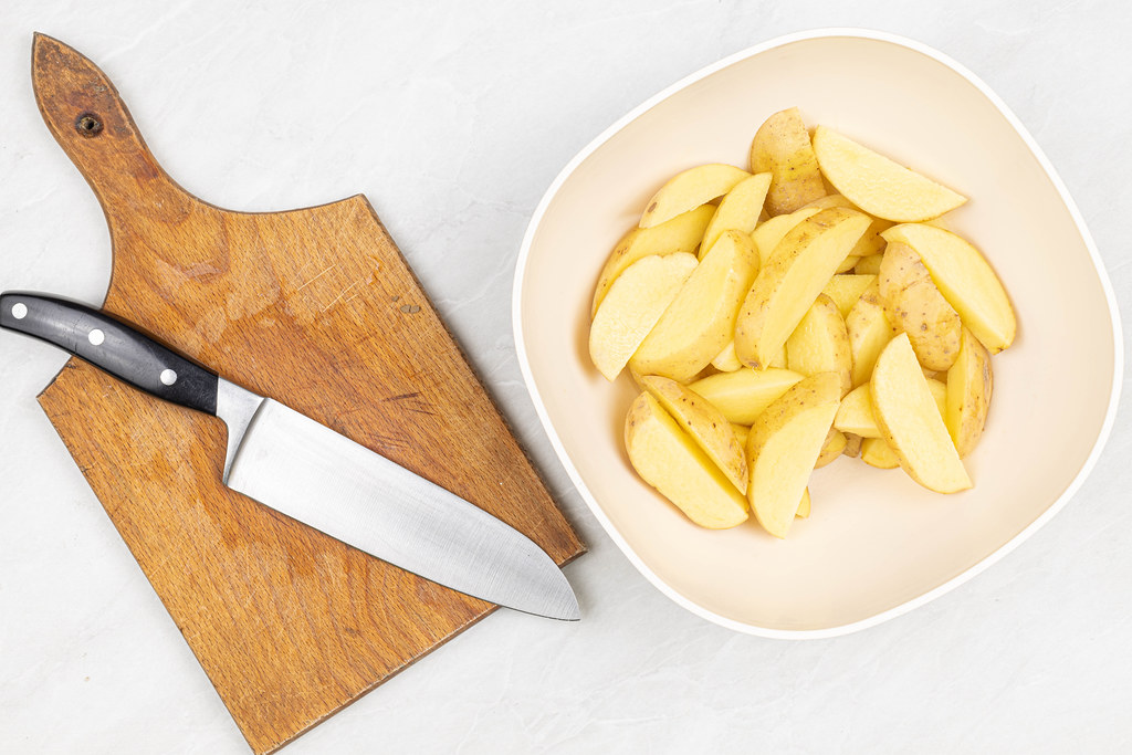 Top view Raw Sliced Potatoes with cutting board and knife