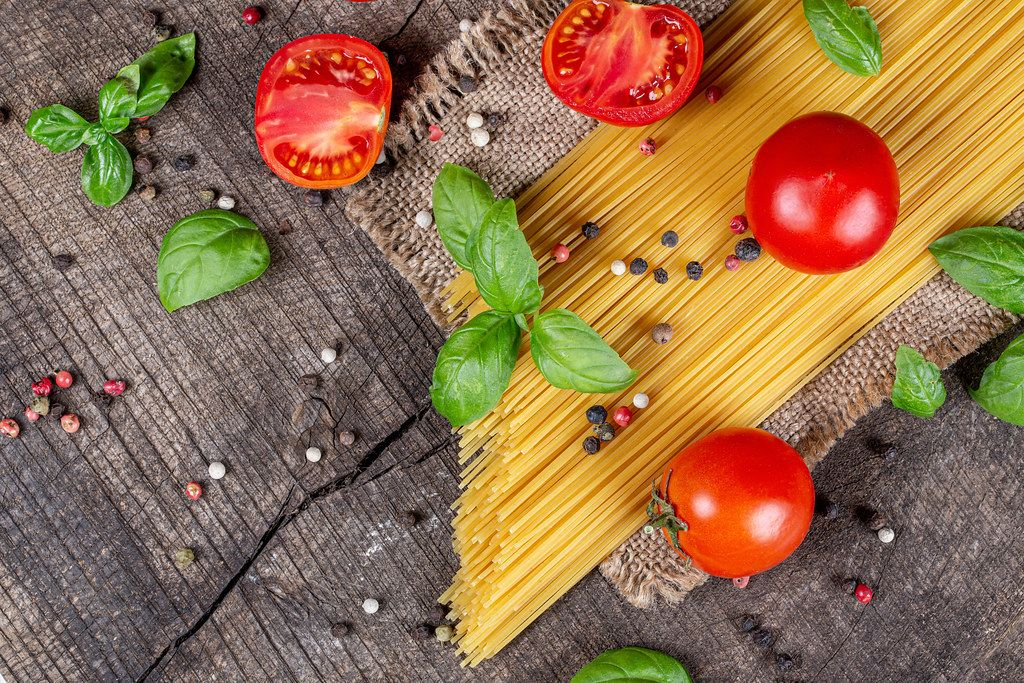 Top view, raw spaghetti, tomatoes, basil and spices on old wooden background