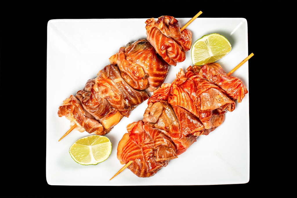 Top view, salmon kebabs on white plate, black background