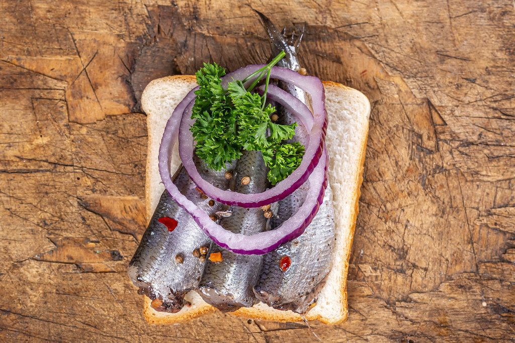 Top view, sandwich with pickled fish, onion slices and parsley on old wooden background