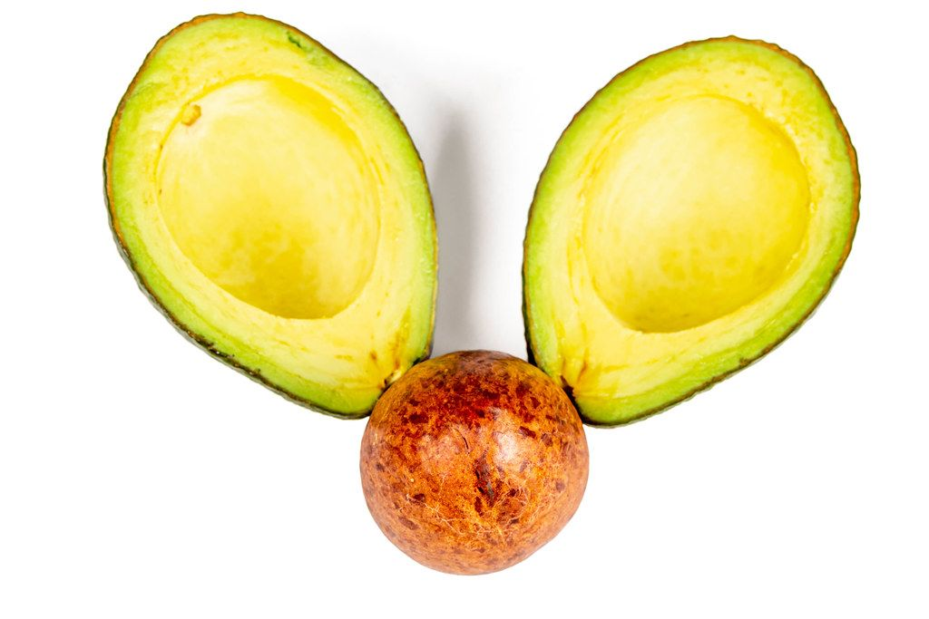 Top view, seed and two halves of ripe avocado