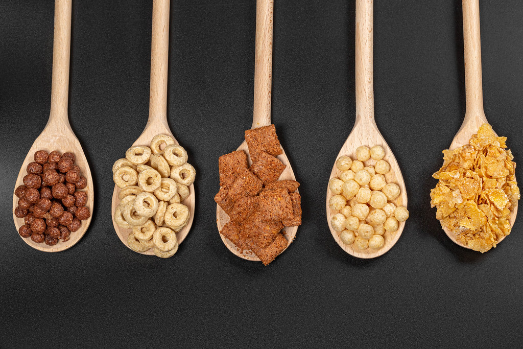 Top view, set of breakfast cereals in wooden spoons on black background