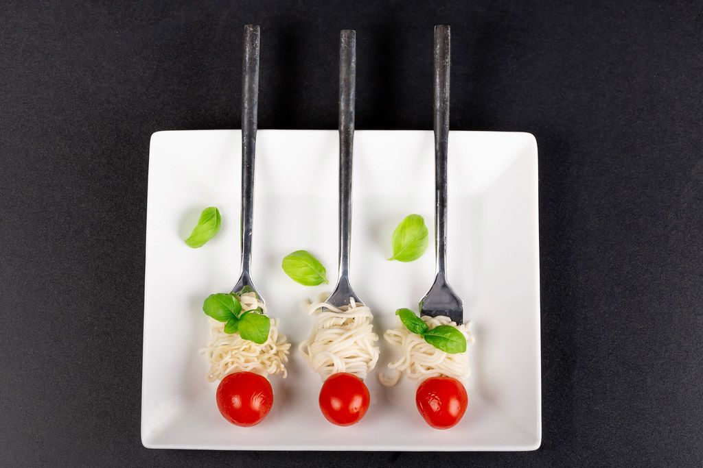 Top view, spaghetti with fresh cherry tomatoes and basil leaves