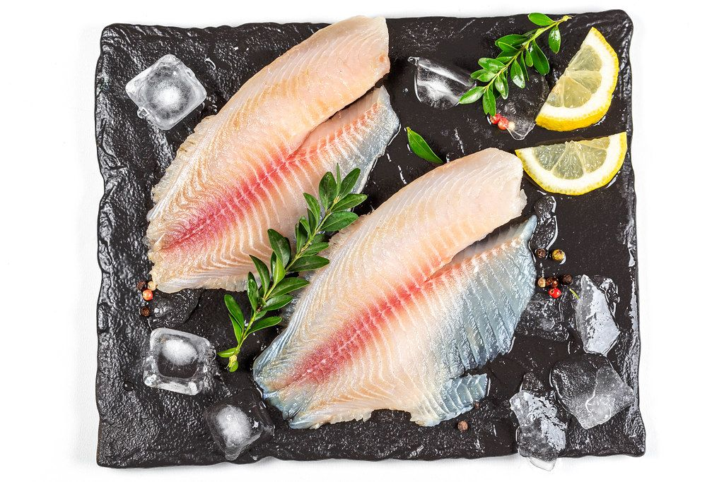 Top view, tilapia fillet with ice and lemon slices on black tray