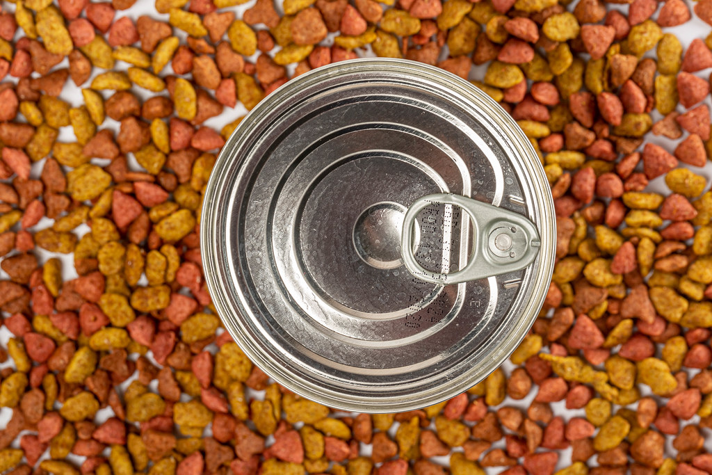 Top view, tinned food for pets on dry food background