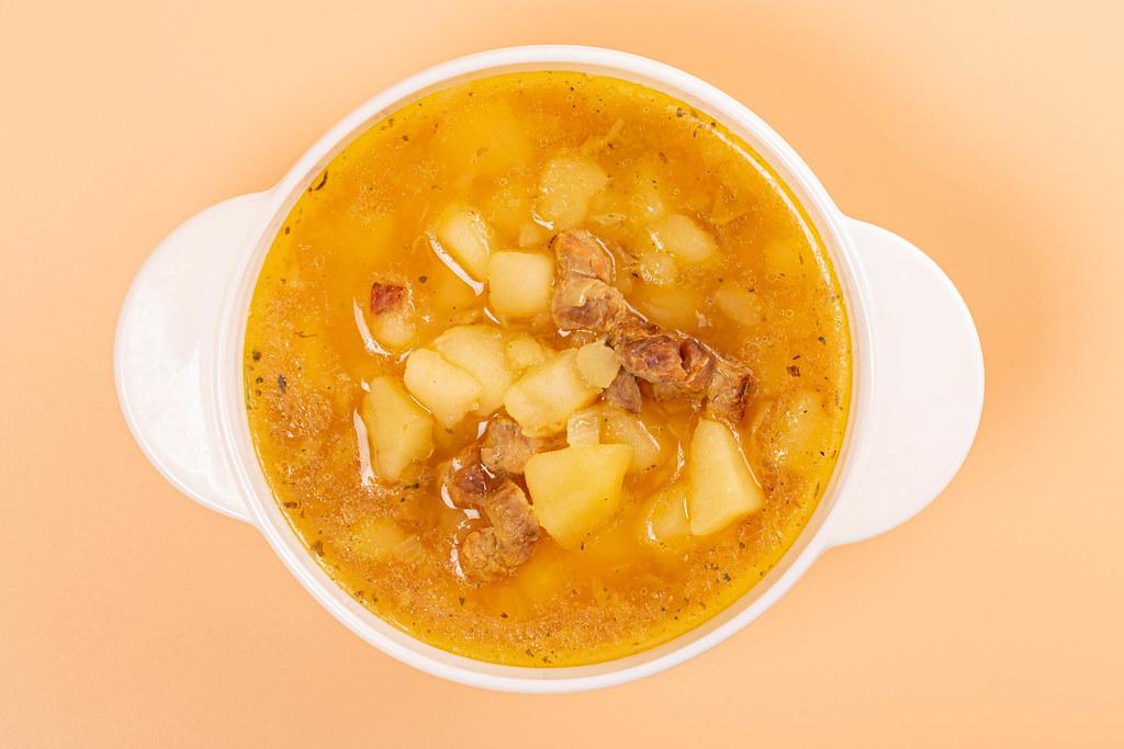 Top view, tureen with potato soup on orange background