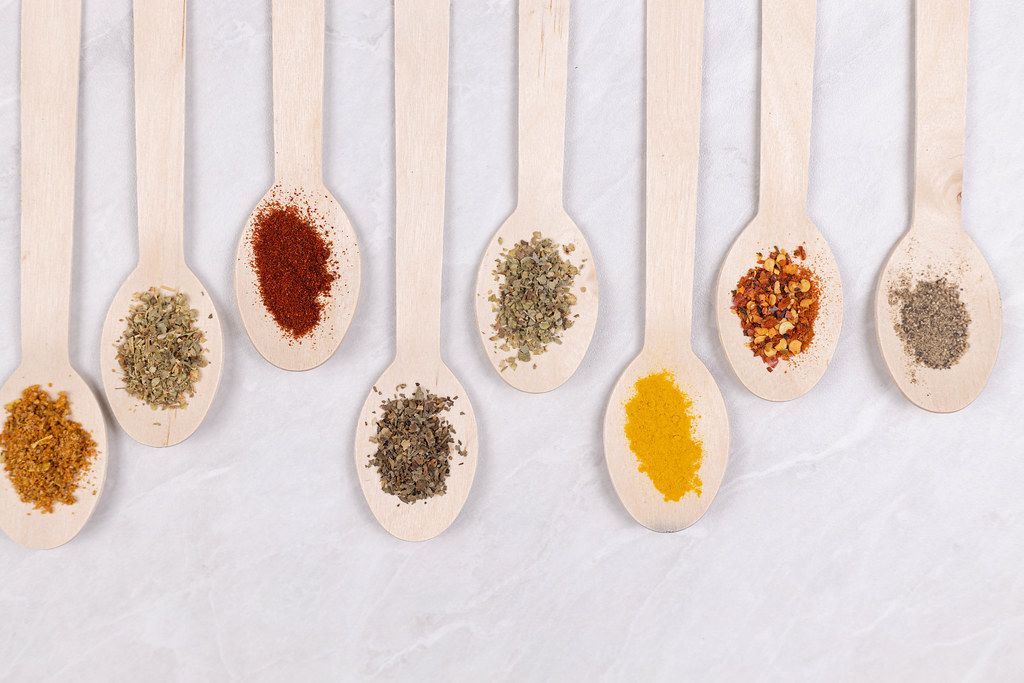 Top view Wooden Spoons with dried spices on grey background