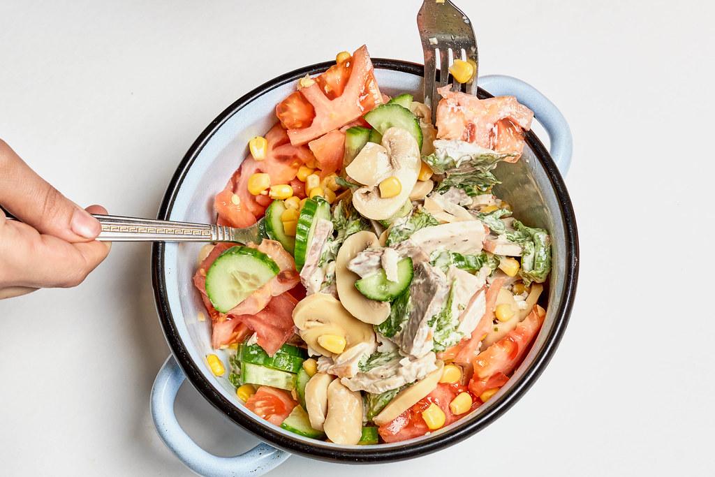 Topf mit frischem Gericht mit Gurken, Champignons, Tomaten, Mais, Fleisch vor weißem Hintergrund