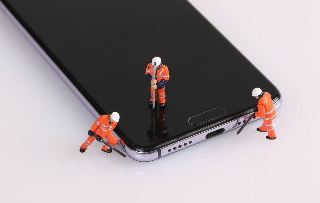Topview of miniature workers repairing smartphone