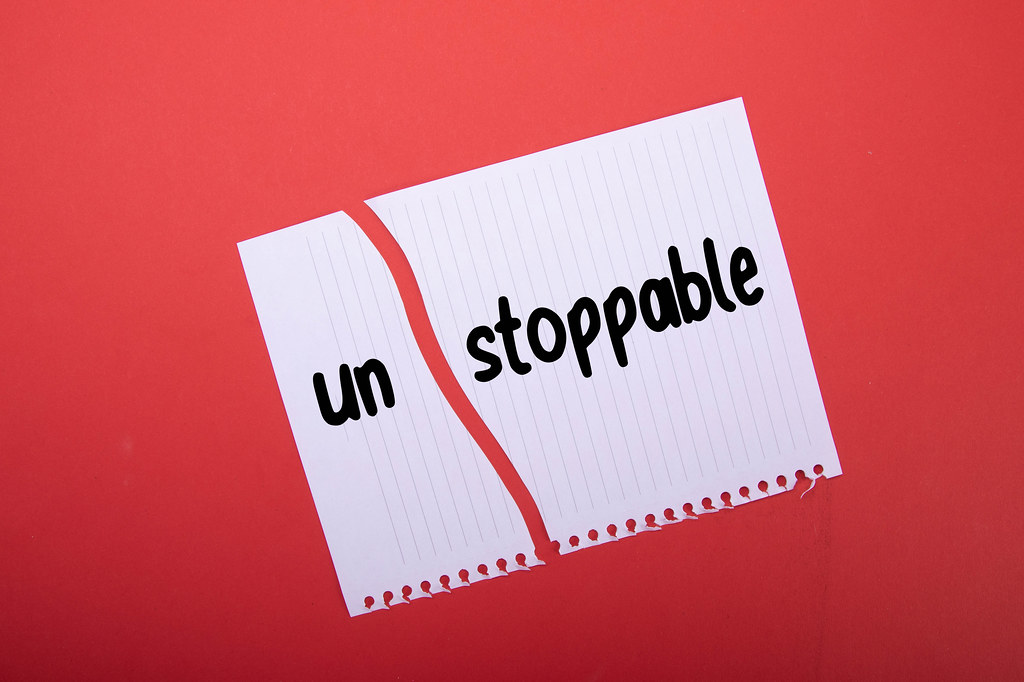 Torn paper with Unstoppable text on red background