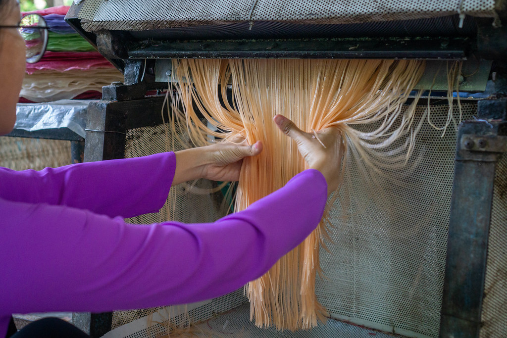 Tourist grabbing Vegetable Vermicelli coming out of a Noodle Machine at a Workshop in the Mekong Delta in Can Tho, Vietnam