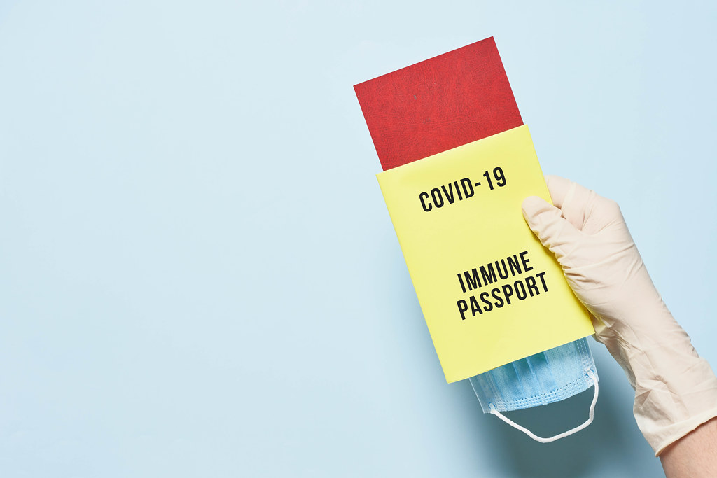 Tourist hand in medical gloves holding immune passport
