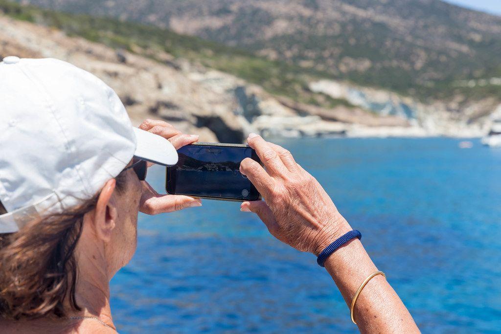 Tourist in Urlaub auf Milos, Griechenland macht ein Foto von der Küste mit seinem Smartphone