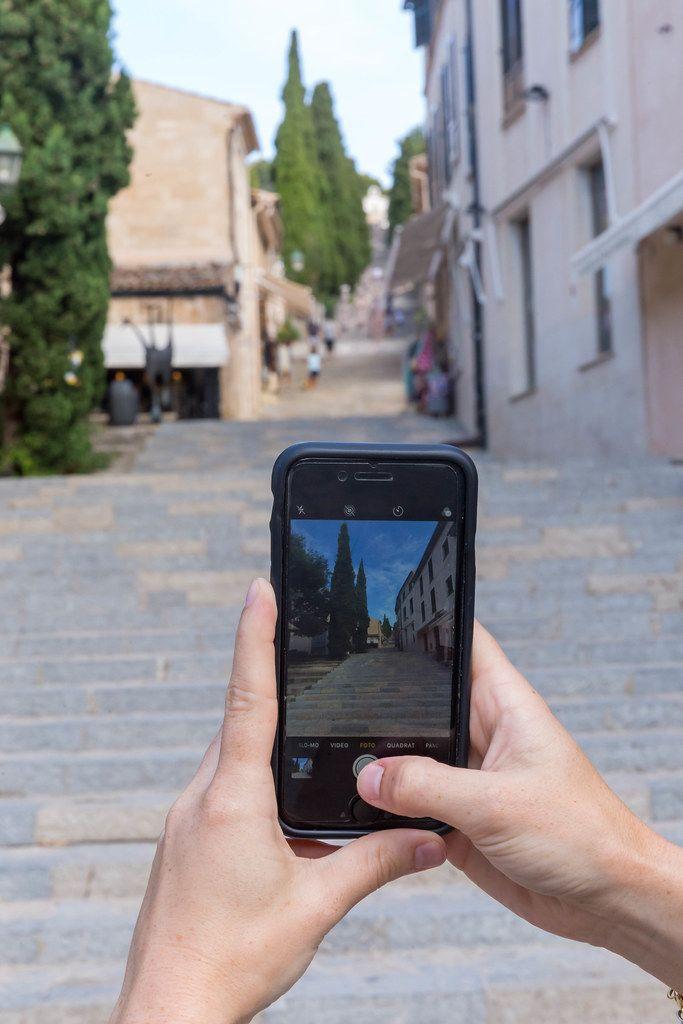 Tourist mit iPhone in den Händen fotografiert die Treppe mit 365 Stufen bei Pollença, Mallorca