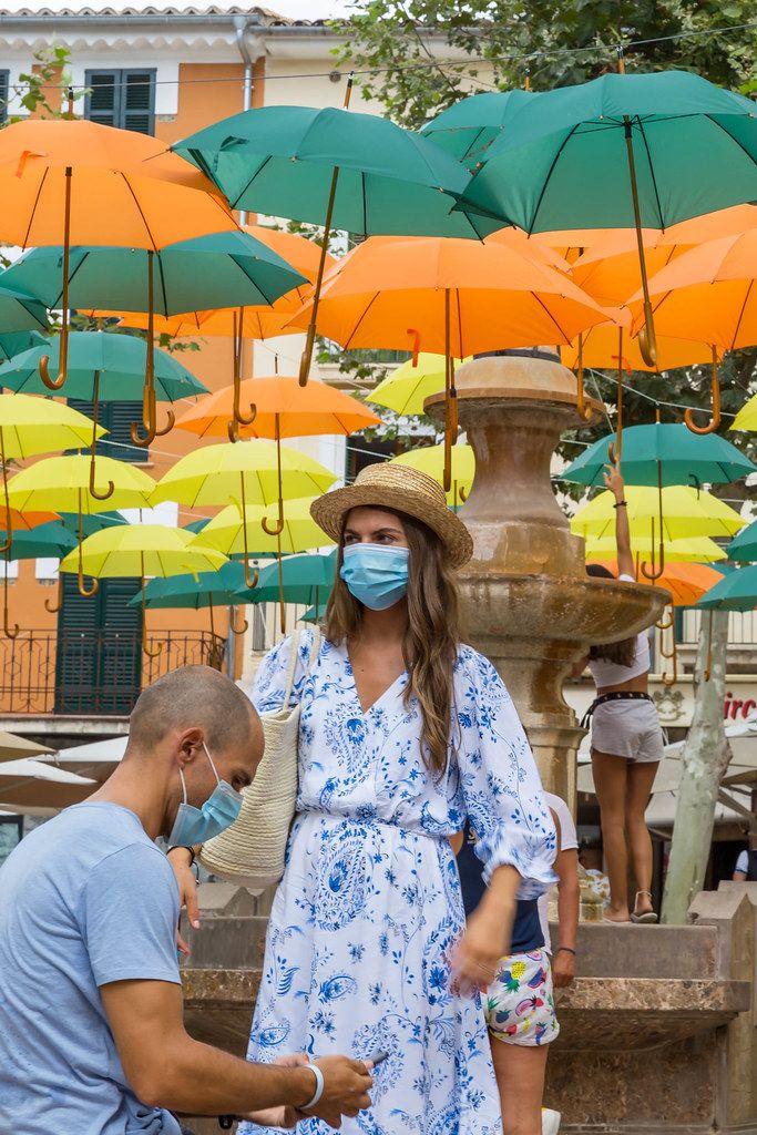 Touristen mit Mundschutz beim Fotospot in Sóller, Mallorca: Regenschirmen-Installation von V. Balaguer