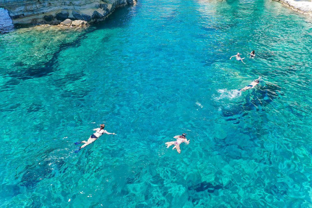 Touristen schnorcheln in den türkisen Gewässern von Kleftiko während des Bootsausflugs um Milos