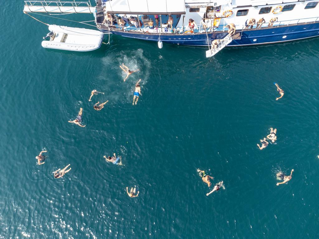 Touristen schwimmen in den Gewässern von Peristera während eines Segelbootausflugs. Drohnenaufnahme