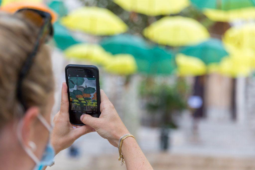 Touristin mit Mundschutz fotografiert bunte Regenschirme in Sóller, Mallorca mit ihrem iPhone