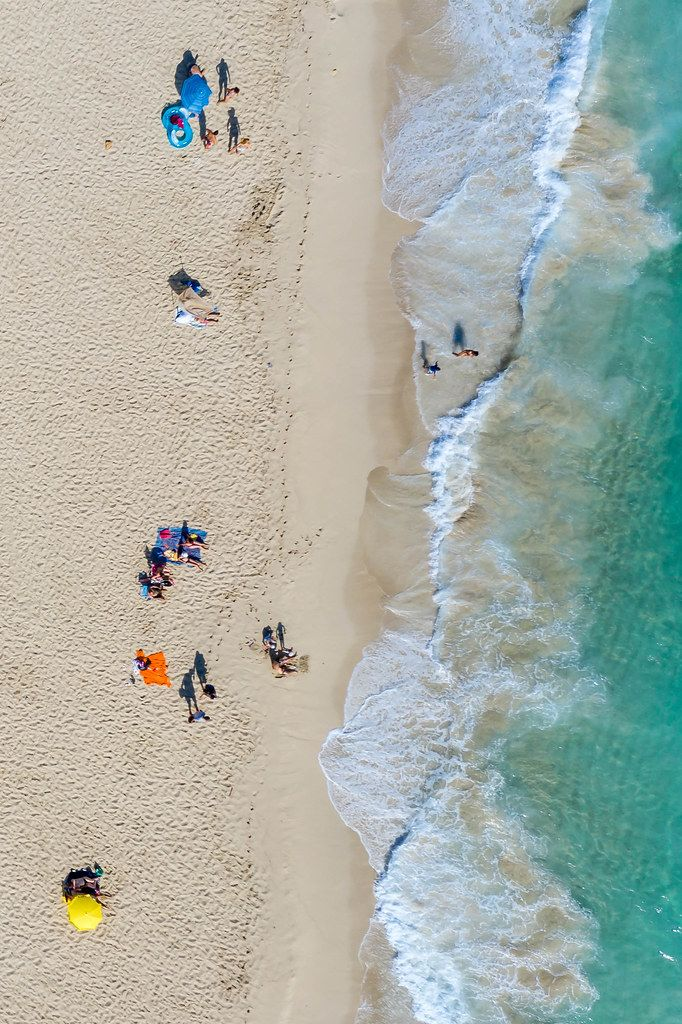 Tourists sunbathing by the shore in Mallorca in summer 2020. Cala Mesquida, drone photo