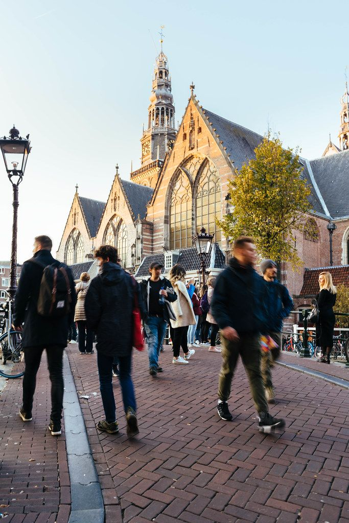 Tourists walking on the square in front of The Oude Church in Amsterdam