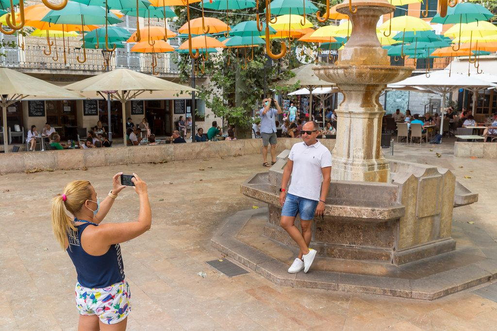 "Tourists with face mask at photo spot in Sóller, Majorca: the new ""suspended umbrellas"" installation"