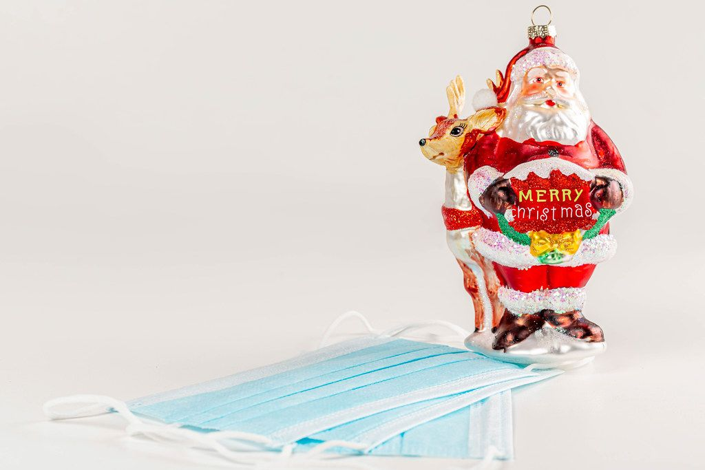 Toy santa claus holding a wish of merry christmas in his hands on a white background with medical masks