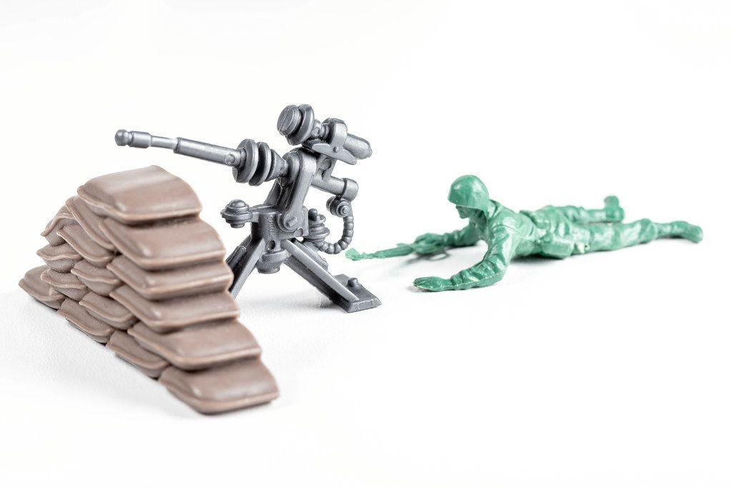 Toy soldier with a machine gun on white. War concept