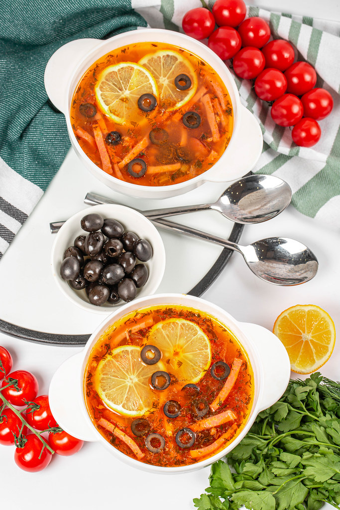 Traditional russian soup solyanka cooked with meat, sausages, lemon, salted cucumbers and olives