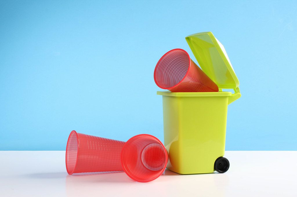 Trash bin with a plastic cups on blue background