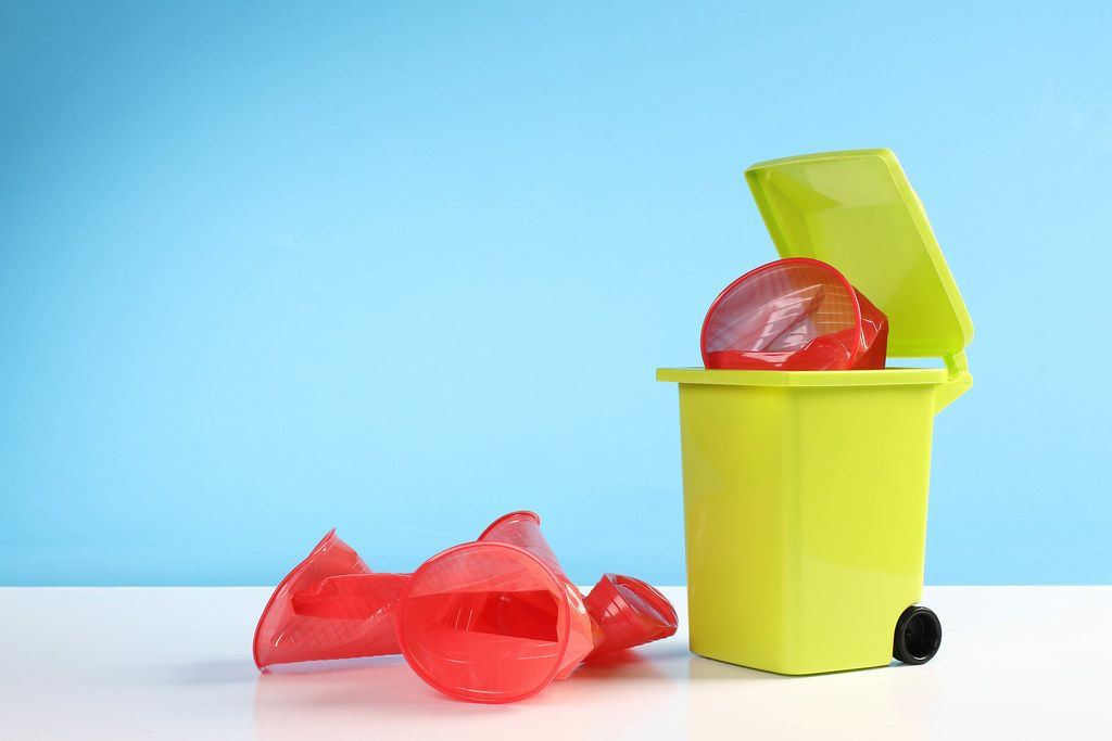 Trash bin with red plastic cups on blue background