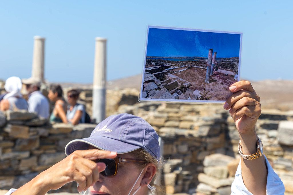 Travel guide at the archaeological site of Delos, Greece, shows a photo with ruins and columns