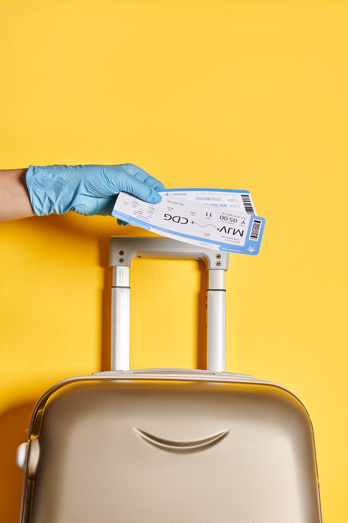 Traveling during coronavirus pandemic - a person with travel luggage holds air flight tickets