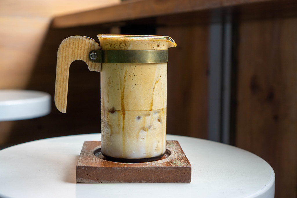 Trendgetränk Dalgona Kaffee in einem Designer Kaffeeglas mit Holzhenkel auf einem Holz-Untersetzer
