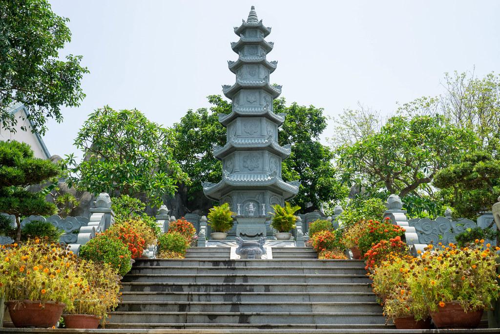 Treppen führen zu einem Steinturm mit kleinem Altar und vielen Pflanzen bei der Linh Ung Pagode auf der Son Tra Halbinsel in Da Nang, Vietnam