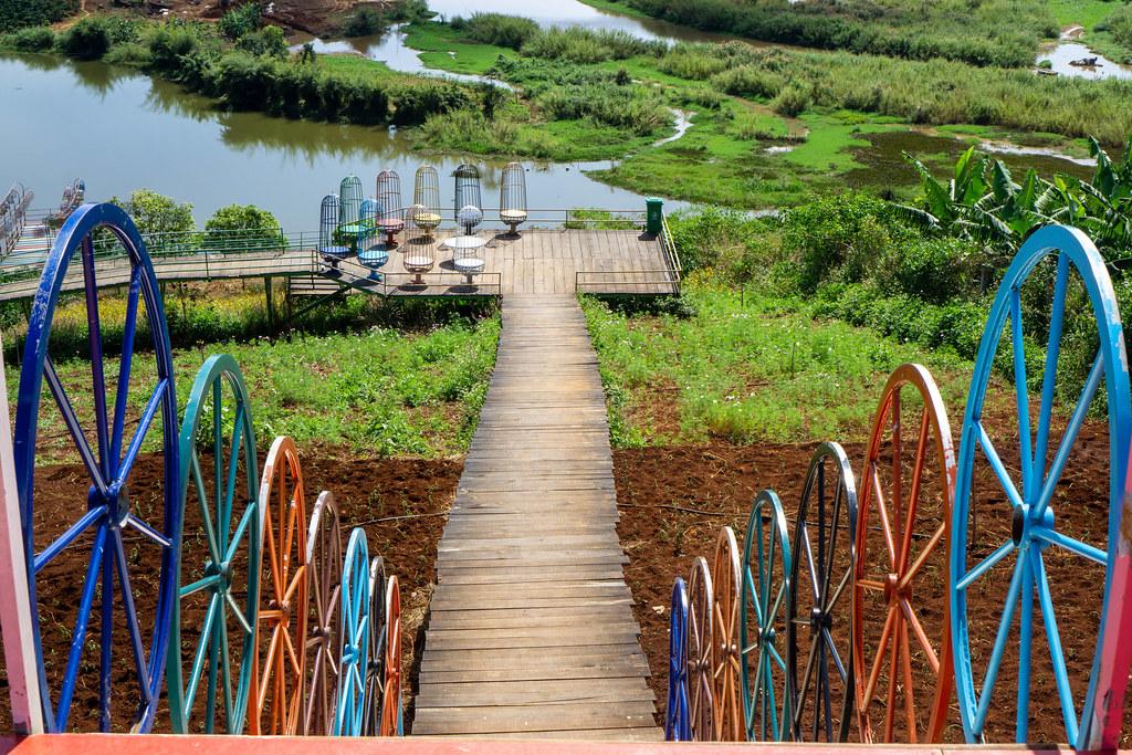 Treppen mit bunten Rädern als Zaun führen zu einer Holzterasse mit bunten Stühlen über einen Holzweg in Dalat, Vietnam