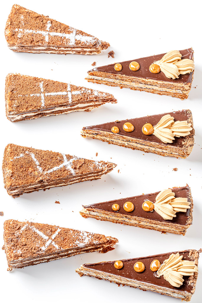 Triangular pieces of chocolate napoleon and nut cake on white background