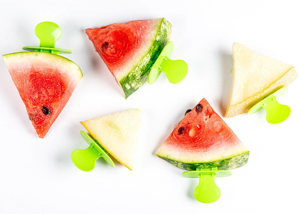 Triangular slices of fresh melon and watermelon on white, top view