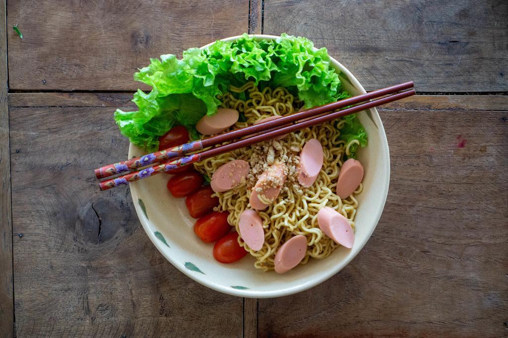 Trockene Instant-Nudeln mit Kirschtomaten, Erdnüssen, Salat und Würstchen als Asiatisches Gericht mit Essstäbchen von oben fotografiert