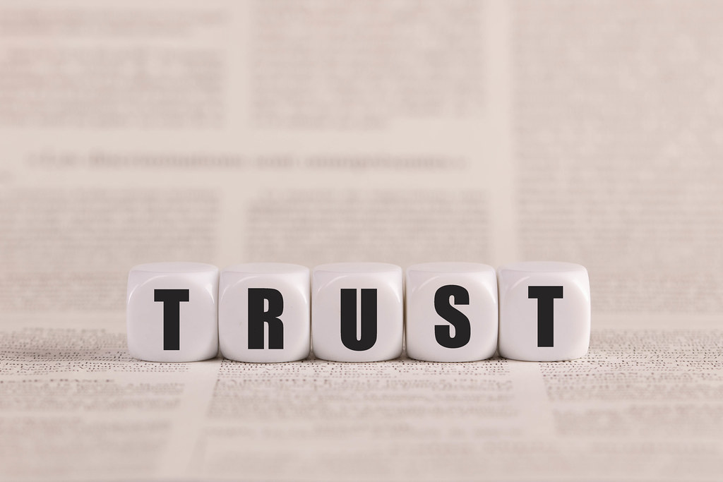 Trust written with cubes on a newspaper