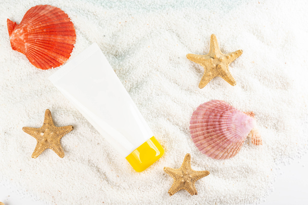 Tube of sunscreen with seashells, top view