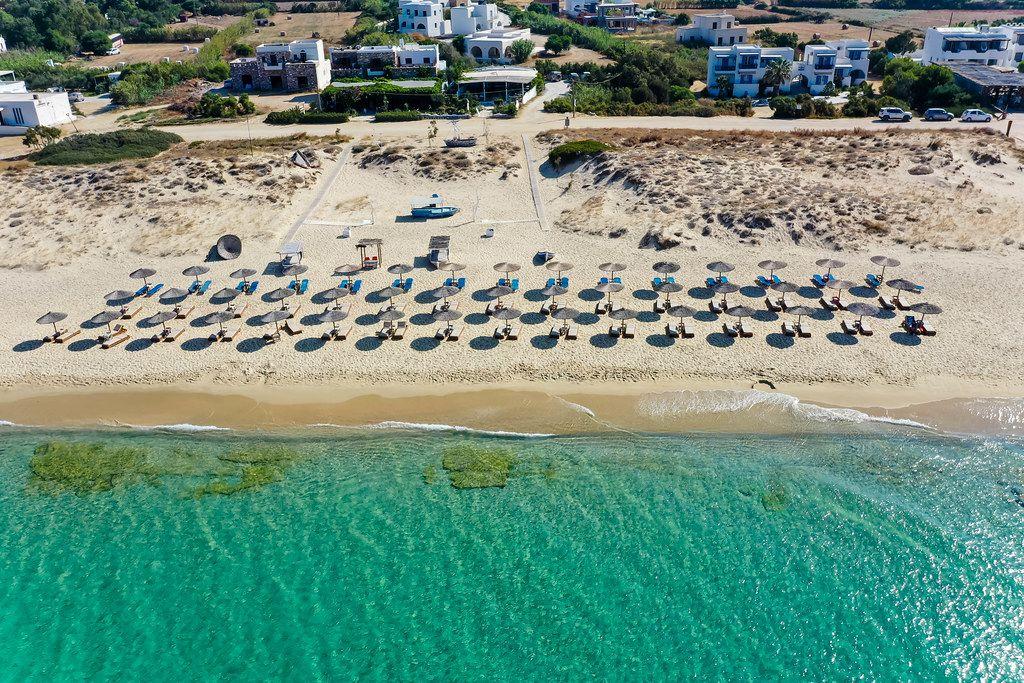 Türkises Wasser und Strohschirme. Luftbild von gepflegtem Plaka Strand auf Naxos