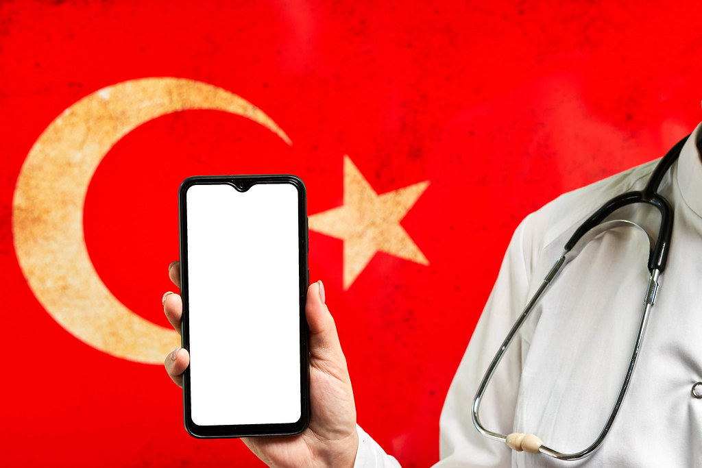 Turkish doctor holding up a smartphone with empty screen