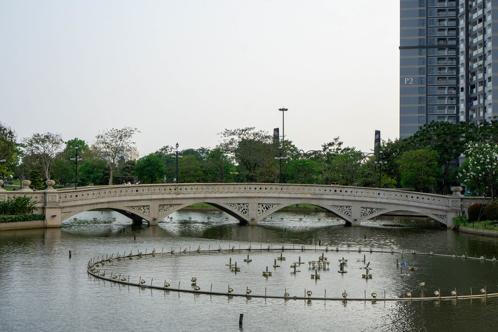 Turned Off Fountain System in a Lake at Vinhomes Central Park with Pedestrian Stone Bridge in the Background in Saigon, Vietnam