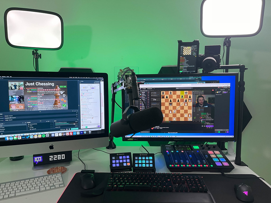 Twitch Chess livestreaming from workstation with two monitors, professional microphone, camera, mixing console