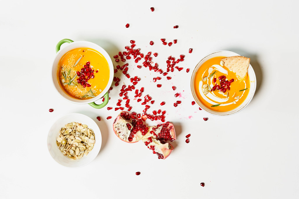 Two bowls of creamy pumpkin soup with pomegranate seeds