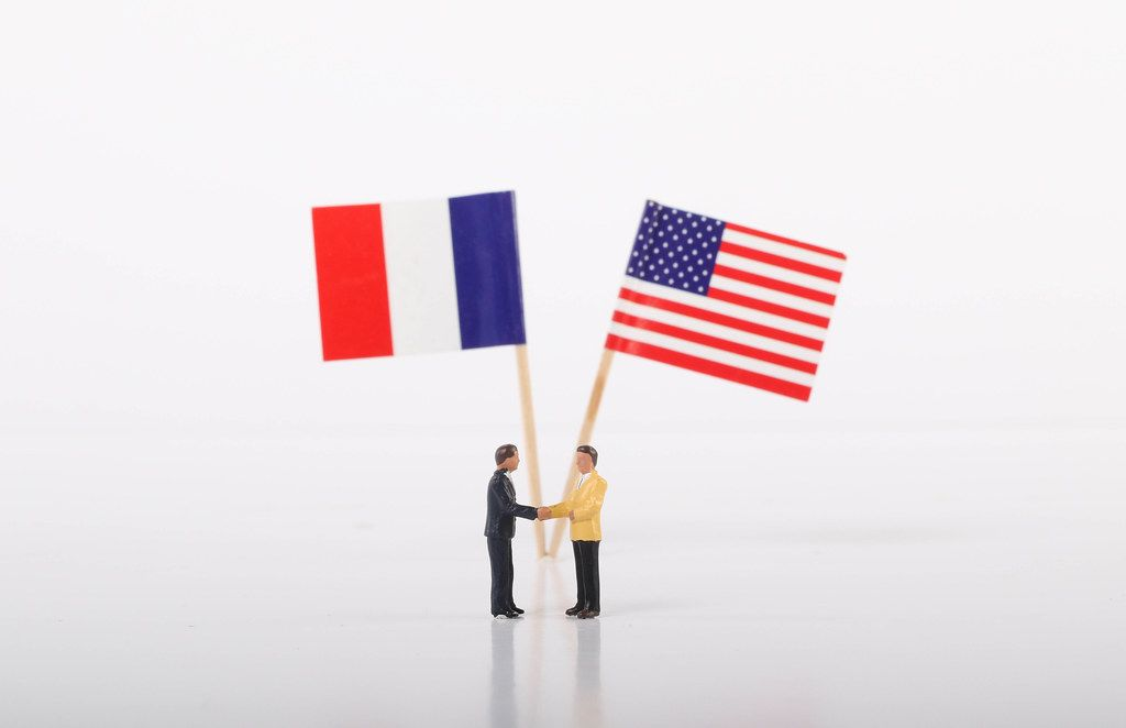Two businessman shaking hands in front of flags of France and USA