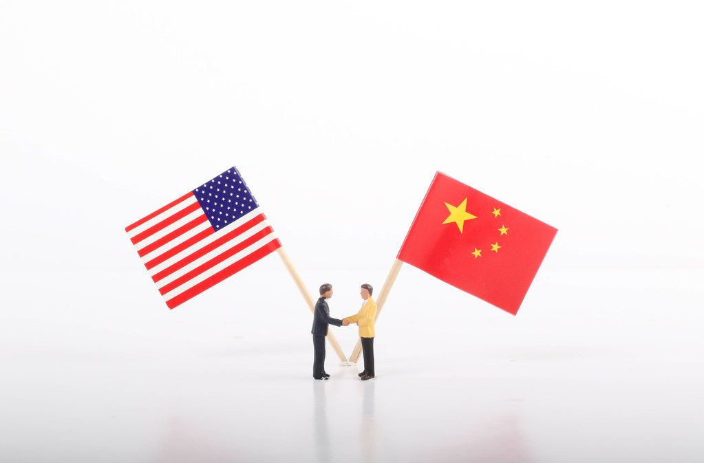 Two businessman shaking hands in front of flags of USA and China