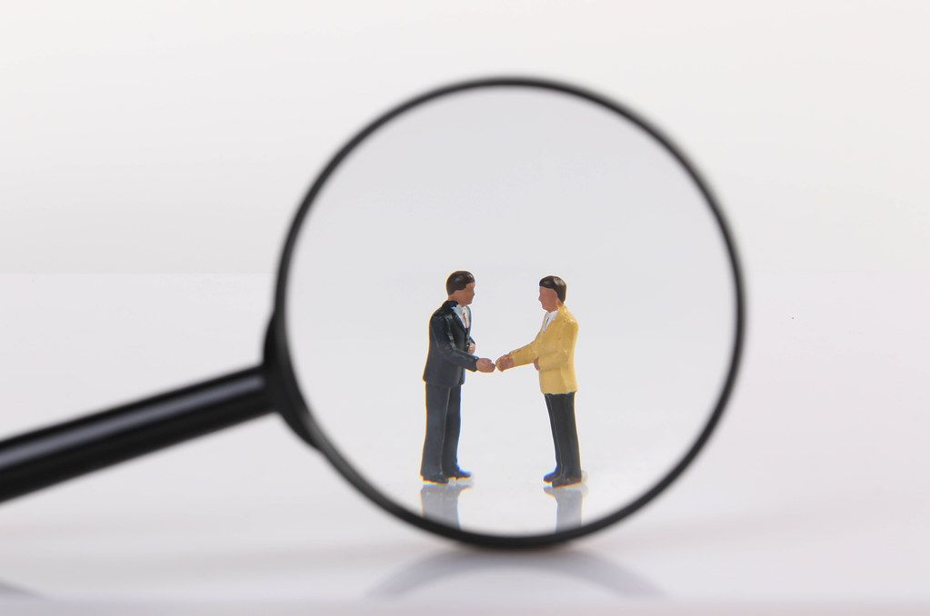 Two businessman shaking hands under magnifying glass