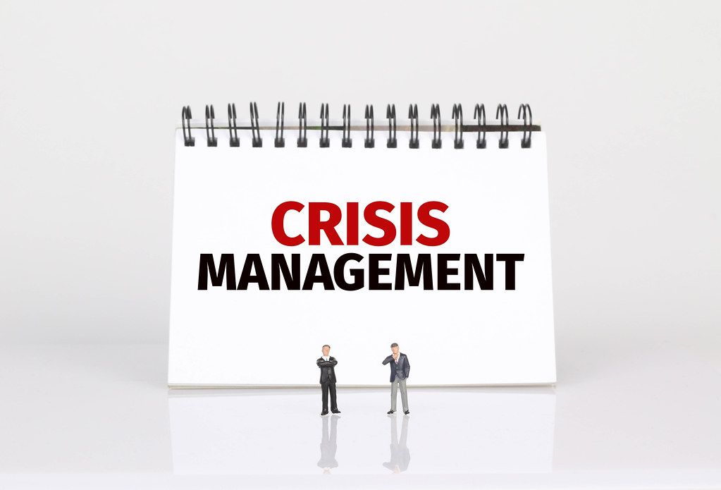 Two businessman standing in front of Crisis Management text