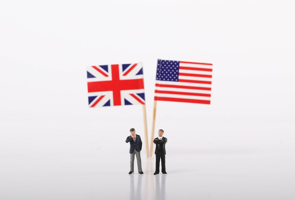 Two businessman standing in front of flags of United Kingdoma and USA